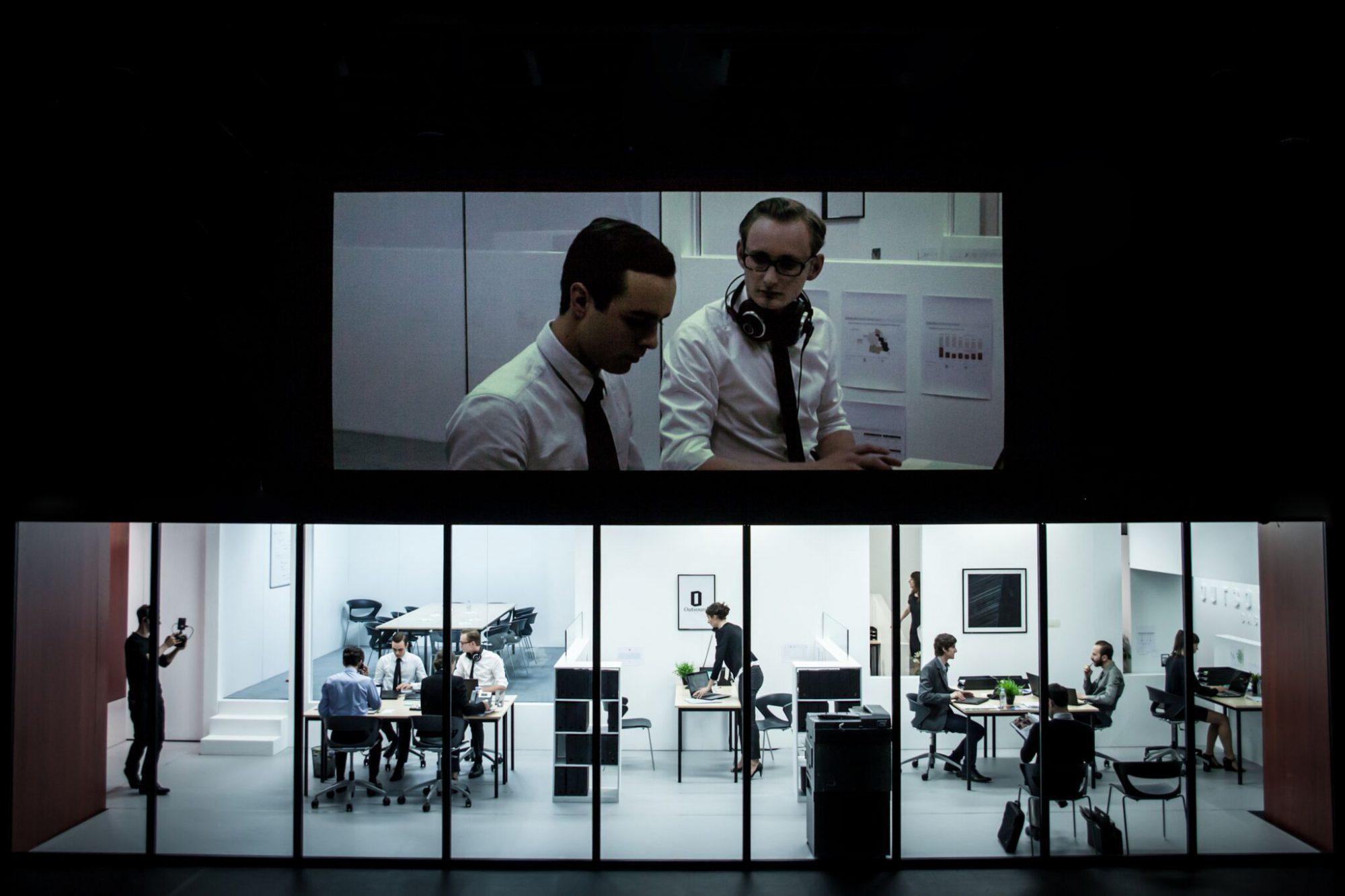 La présence de cameramans sur scène évoque la surveillance et le besoin de justifier en permanence sa place dans le monde du travail actuel.
